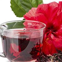Fotografía de un vaso con una té o infusión de flor de jamaica.