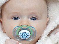 Fotografía de bebé con una chupeta en su boca.