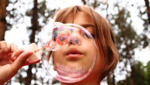 Fotografía de niña haciendo burbujas de jabón